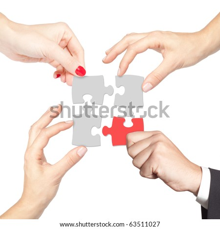 Teamwork solving a puzzle isolated on white - stock photo