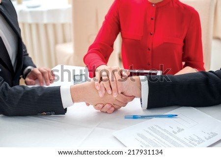 Teamwork. Three successful and confident businesspeople shake hands. Businesspeople in formal attire sitting in an office at a desk close-up view of hands - stock photo