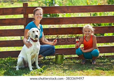 Teamwork - woman with little girl and dog painting a fence in summer time