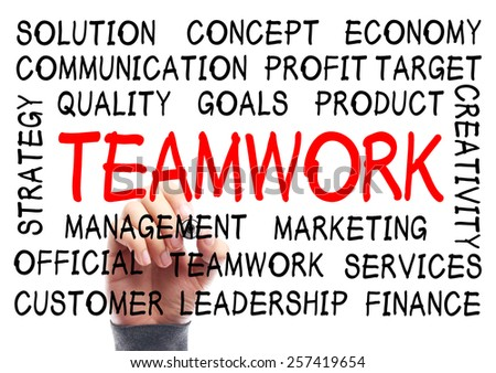 Teamwork word cloud is written on transparent whiteboard by the hand of a businessman. - stock photo