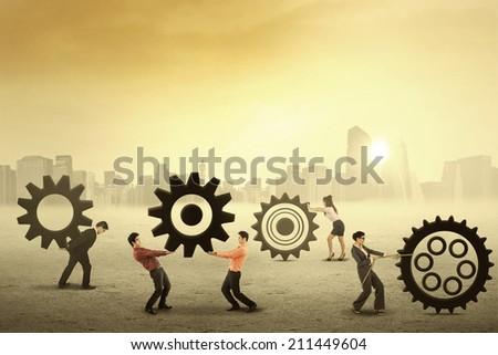 Teamwork works together to build a gear system, shot outdoors in the morning - stock photo