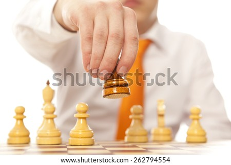 Teamwork. Young business man playing chess - stock photo