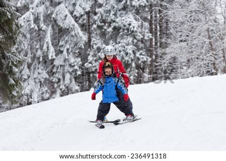 Teanage girl trains  her little sister to ski on the slope in the mountains - stock photo