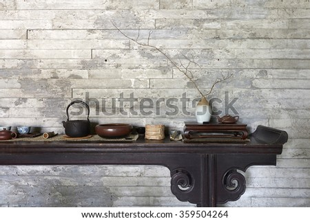 Teapot and bamboo leaves on Chinese old table?Green walls background