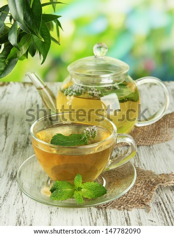 Teapot and cup of herbal tea with fresh mint flowers on wooden table - stock photo