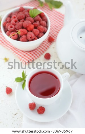 Teapot and cup of raspberry tea with fresh berries on white rustic background