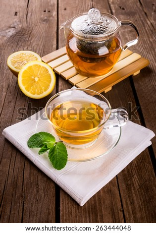 Teapot and cup of tea with fresh mint and lemon on wooden table - stock photo