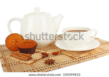 Teapot and cup of tea with spice and muffins on wooden mat, food photo