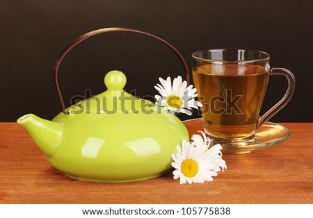Teapot and cup with chamomile tea on wooden table on brown background - stock photo