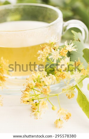 teapot and cup with linden tea and flowers - stock photo