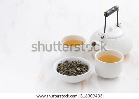 teapot and cups of green tea on a white wooden background, horizontal