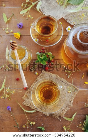 Teapot and cups of herbal tea with linden flowers, lavender and strawberries on wooden table - stock photo