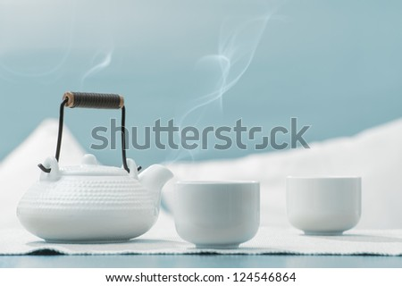 Teapot and cups on table at comfortable relaxation lounge - stock photo