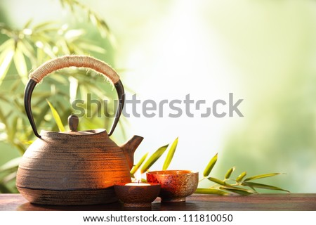 Teapot and cups on table with bamboo leaves. - stock photo