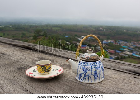 Teapot and cups on wood table with a good view. - stock photo