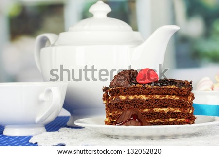 Teapot, cup of tea and delicious cake on window background