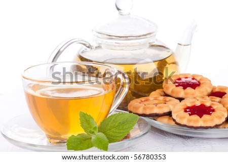 Teapot, cup of tea  with mint and saucer with pastries on a white background. - stock photo