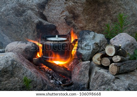 Teapot on campfires amongst stone - stock photo