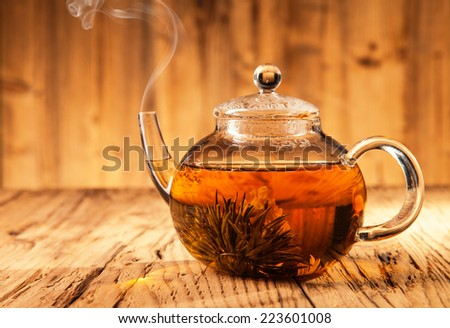 Teapot with blooming tea on wooden planks - stock photo