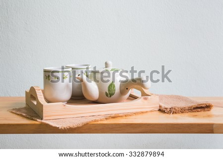 Teapot with cup of tea on wooden table over white wall background
