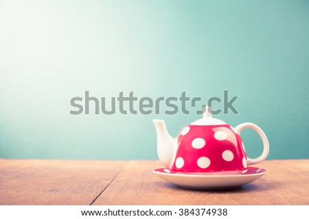 Teapot with polka dots on wooden table. Retro style filtered photo