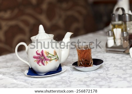 Teapot with teacup on a table in the restaurant - stock photo