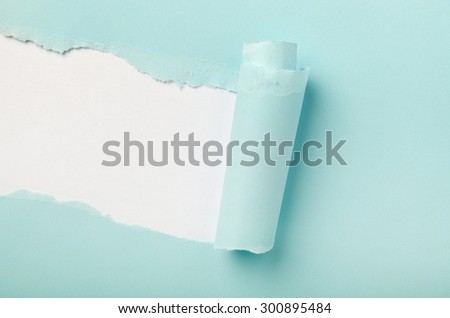 Tear in a piece of blue paper revealing white background underneath  - stock photo