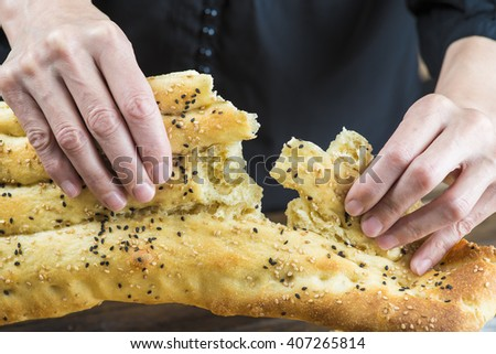 Tearing of a piece of barbari or Persian bread with hands - stock photo