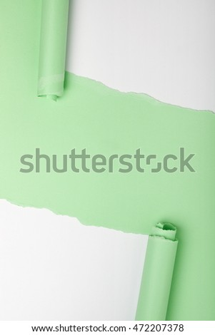 Tears in a piece of green paper revealing white background underneath