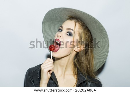 Teasing young blonde girl portrait with bright make up in hat and leather jacket looking forward holding and licking round red sugar candy standing on light gray background , horizontal picture - stock photo