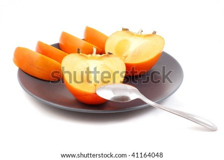 Teaspoon and ripe persimmon - stock photo