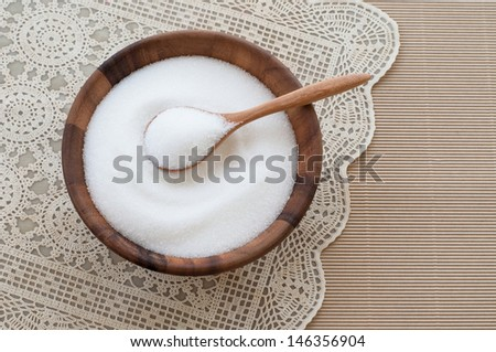 Teaspoon filled with sugar and sugar in wooden bowl. - stock photo