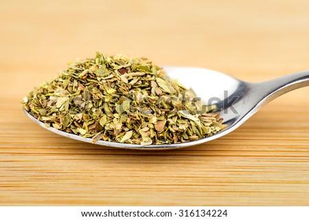 Teaspoon of freshly dried basil herb - stock photo