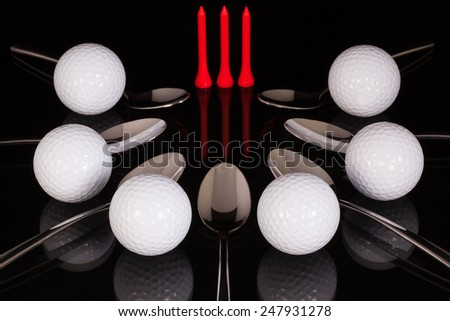 Teaspoons and golf equipments on the black glass desk