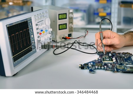 Tech fixes motherboard in service center. Shallow DOF, focus on hand, part of moherboard and front part of oscilloscope. This image is toned. - stock photo