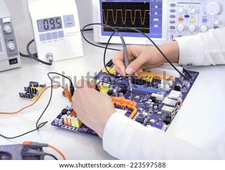 Tech tests electronic equipment in service center - stock photo