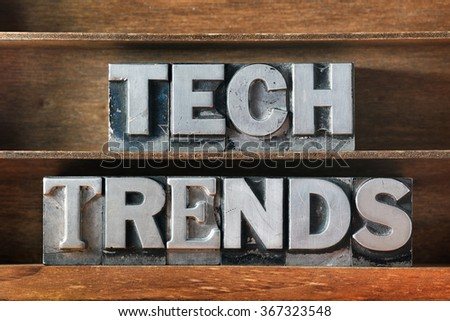 tech trends phrase made from metallic letterpress type on wooden tray