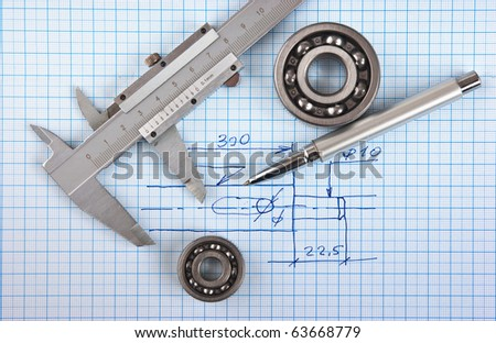 Technical drawing and callipers with  bearing on graph paper - stock photo