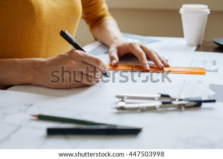 Technical drawing. Woman hands drawing blueprints - stock photo
