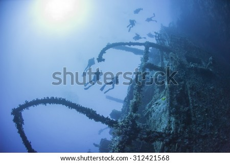 Technical scuba divers exploring a large deep underwater shipwreck - stock photo