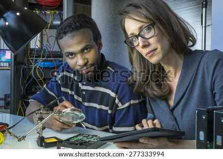 Technical team working together on a tablet - stock photo