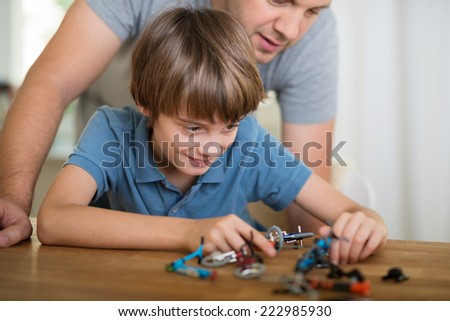 Technically minded little boy playing at home with a dismantled electronic device closely watched by his father who is leaning over him - stock photo
