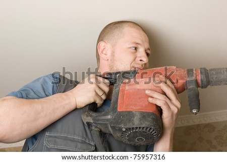 Technician air conditioning drills the wall. Work on installing a new air conditioner. - stock photo
