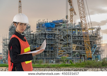 Technician and construction site with cranes on sky background, Power Plant Construction, Lots of tower cranes build large residential buildings at twilight.