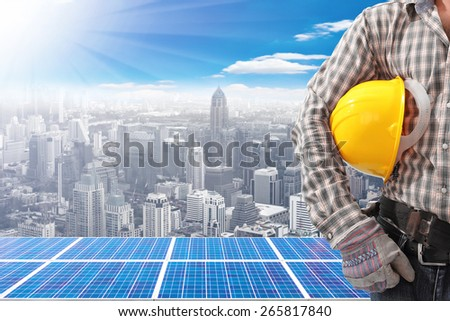 Technician and solar energy panels on high building against beautiful sky with ecology concept - stock photo