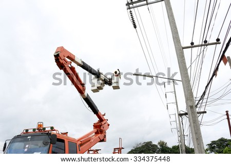 Technician connecting power cable on mobile crane