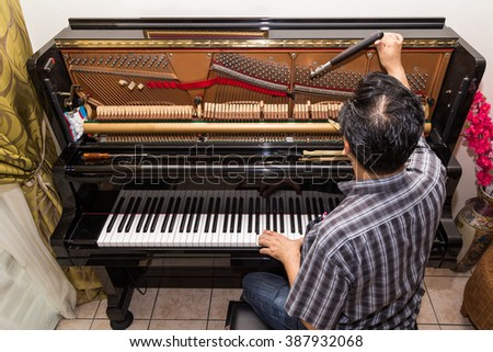 Technician cum musician tuning an upright piano using lever and tools - stock photo