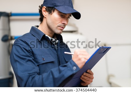 Technician fixing an hot-water heater - stock photo