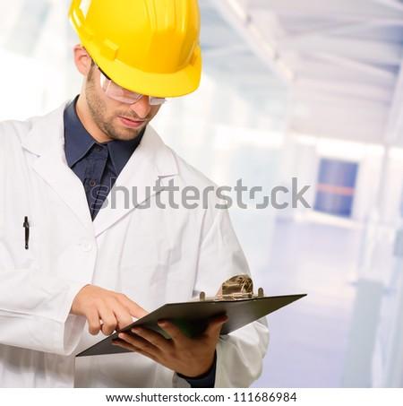Technician Holding Writing Pad, Indoor - stock photo