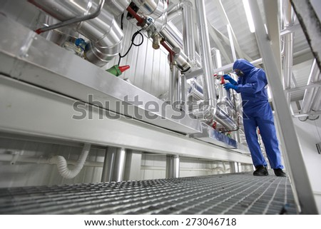 Technician in blue uniform checking technological system - stock photo